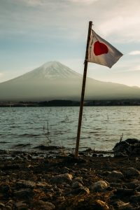 Japan flag pictured in front of a mountain and a lake.