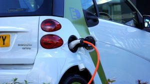 Driving the Electric Revolution: an electric car shown from behind, plugged in charging